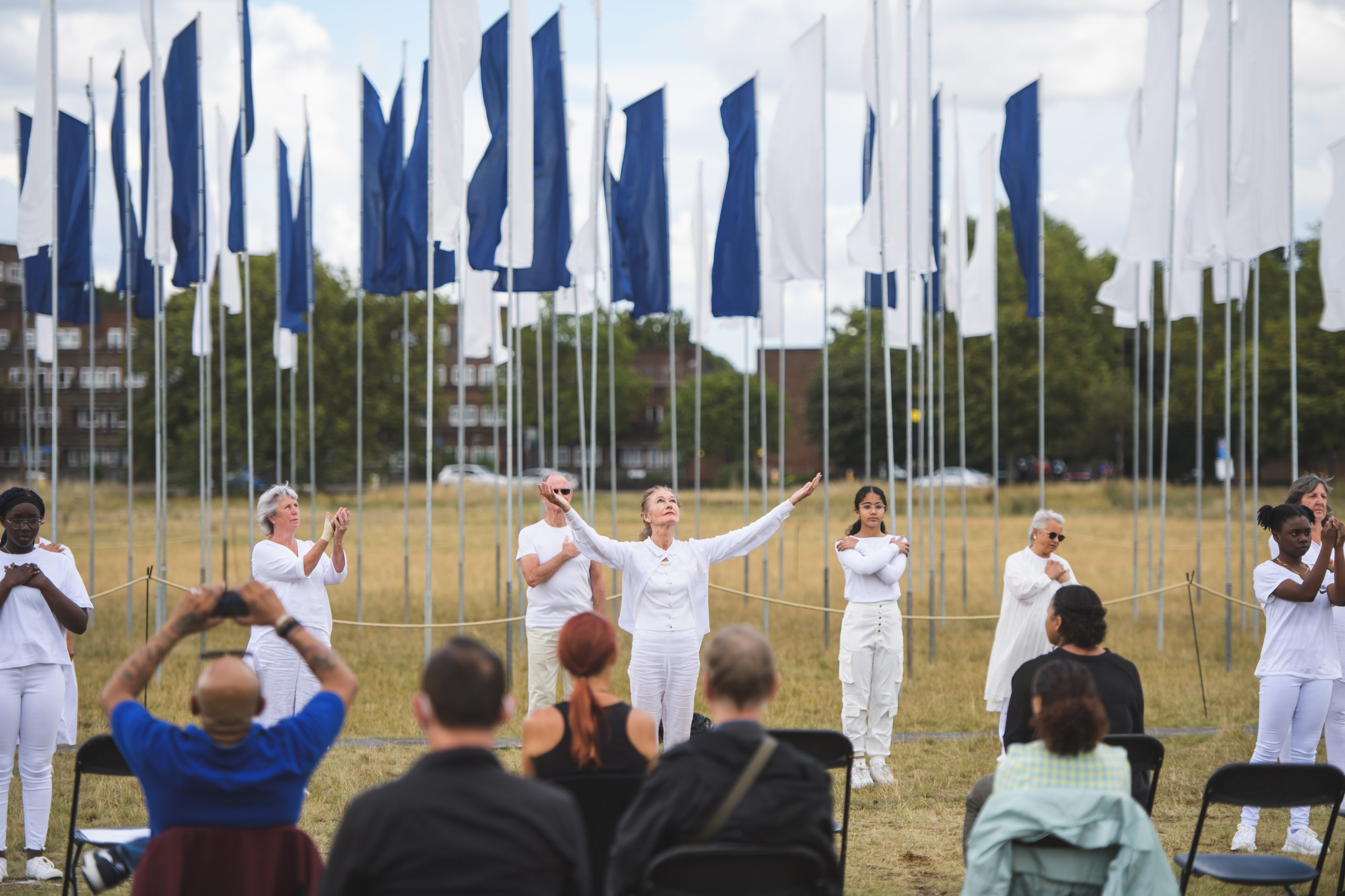 Five people dressed in white dancing in front of blue and white flags with audience watching in the foreground