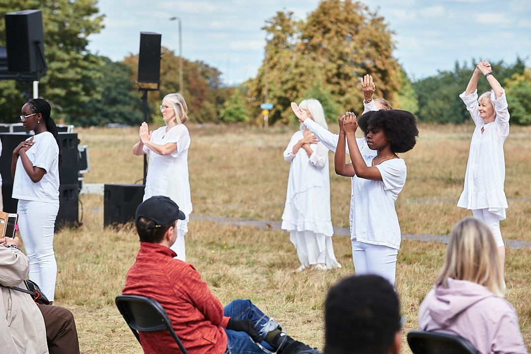 Dancers dressed in white perform to a small audience in a field