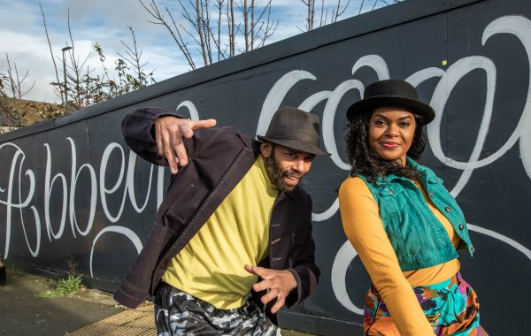A man and a woman both wearing hats pose in front of a black and white hoarding with Abbey Wood graffiti