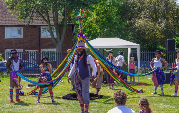 A man in a top hat stands in a park with a colourful maypole behind him. Behind the maypole there is a small white marquee
