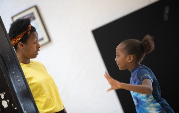 A dance teacher speaks to a young class participant