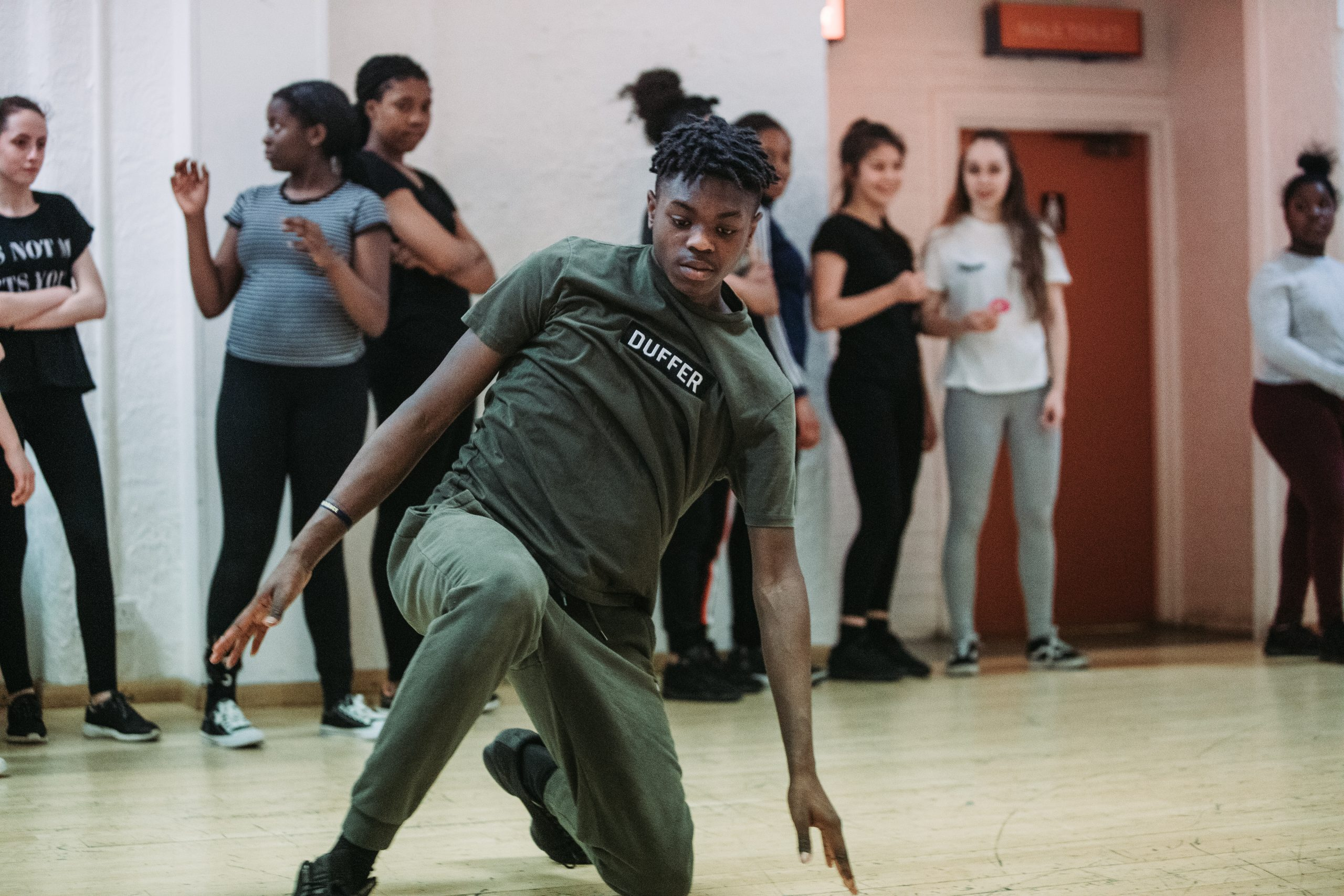 A young male dancer rehearses with friends looking on