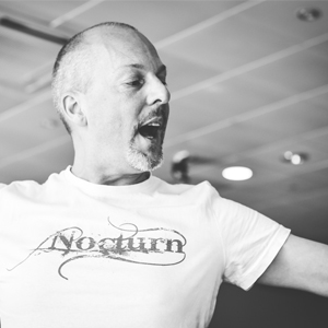 Black and white photo of John Darvell's head and shoulders. John is wearing a light coloured tshirt with his Nocturn company logo on it.