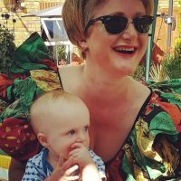 A woman in sunglasses holding a baby