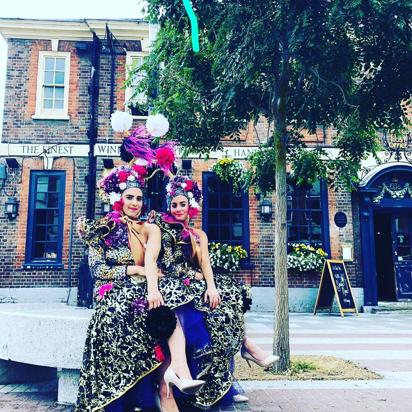 Two women in elaborate costumes stand back to back in a town square