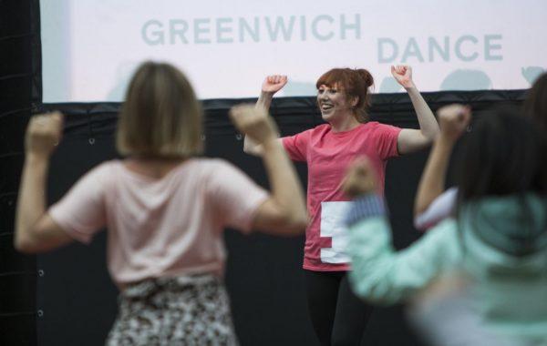 A woman teaching dance in front of a Greenwich Dance logo