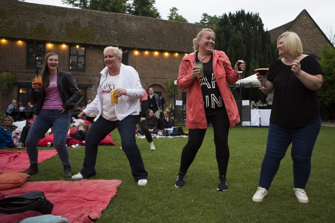 A group of women dancing on a lawn
