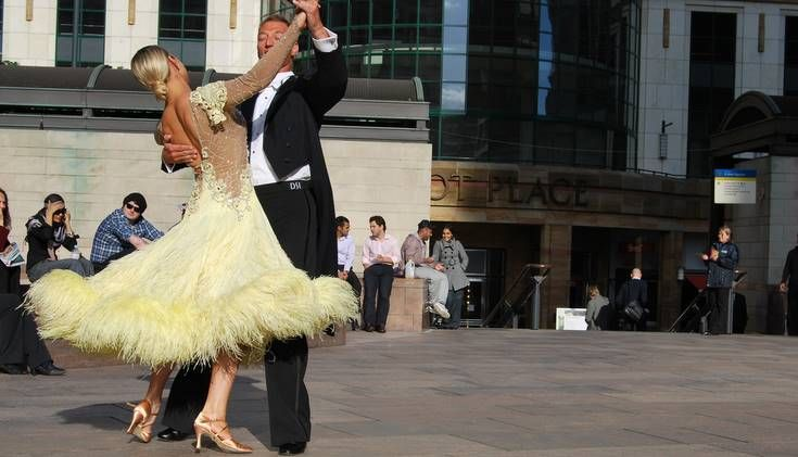 A couple ballroom dance outside in a town square