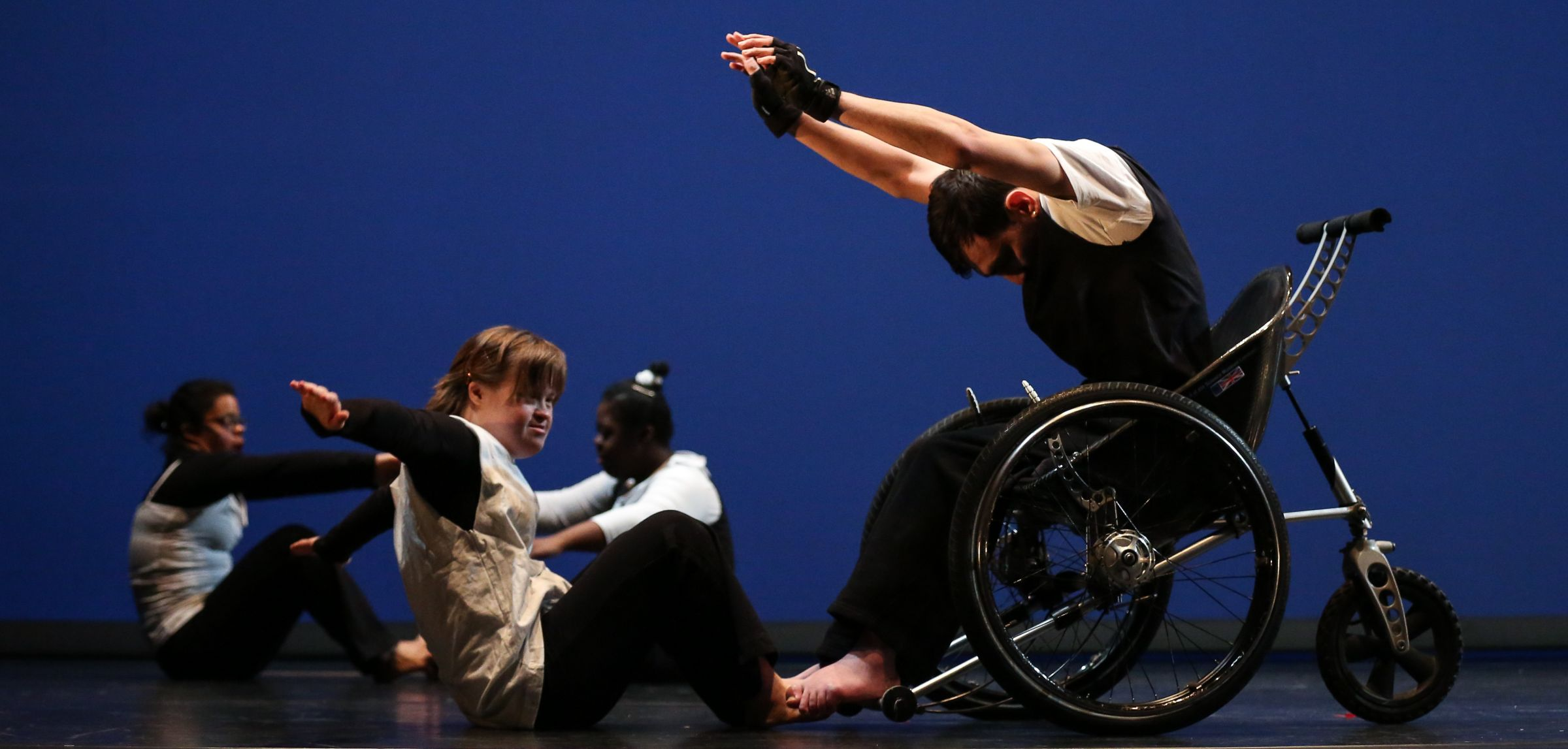 Dancers on stage. One is a wheelchair user