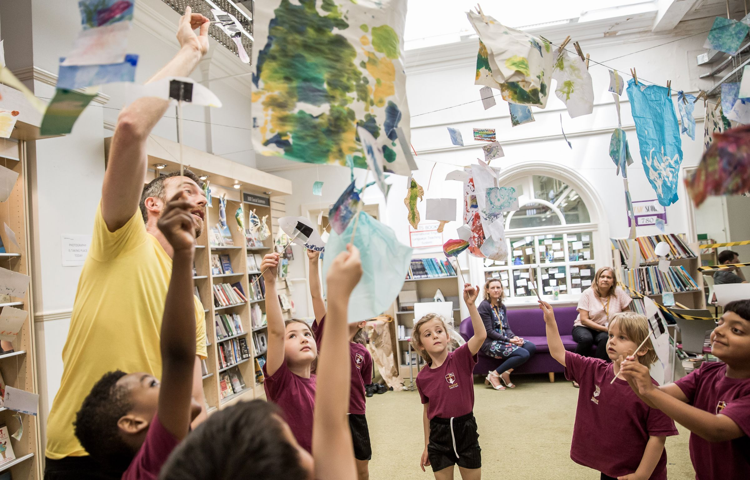 School children reach up to pictures that are hanging from the ceiling