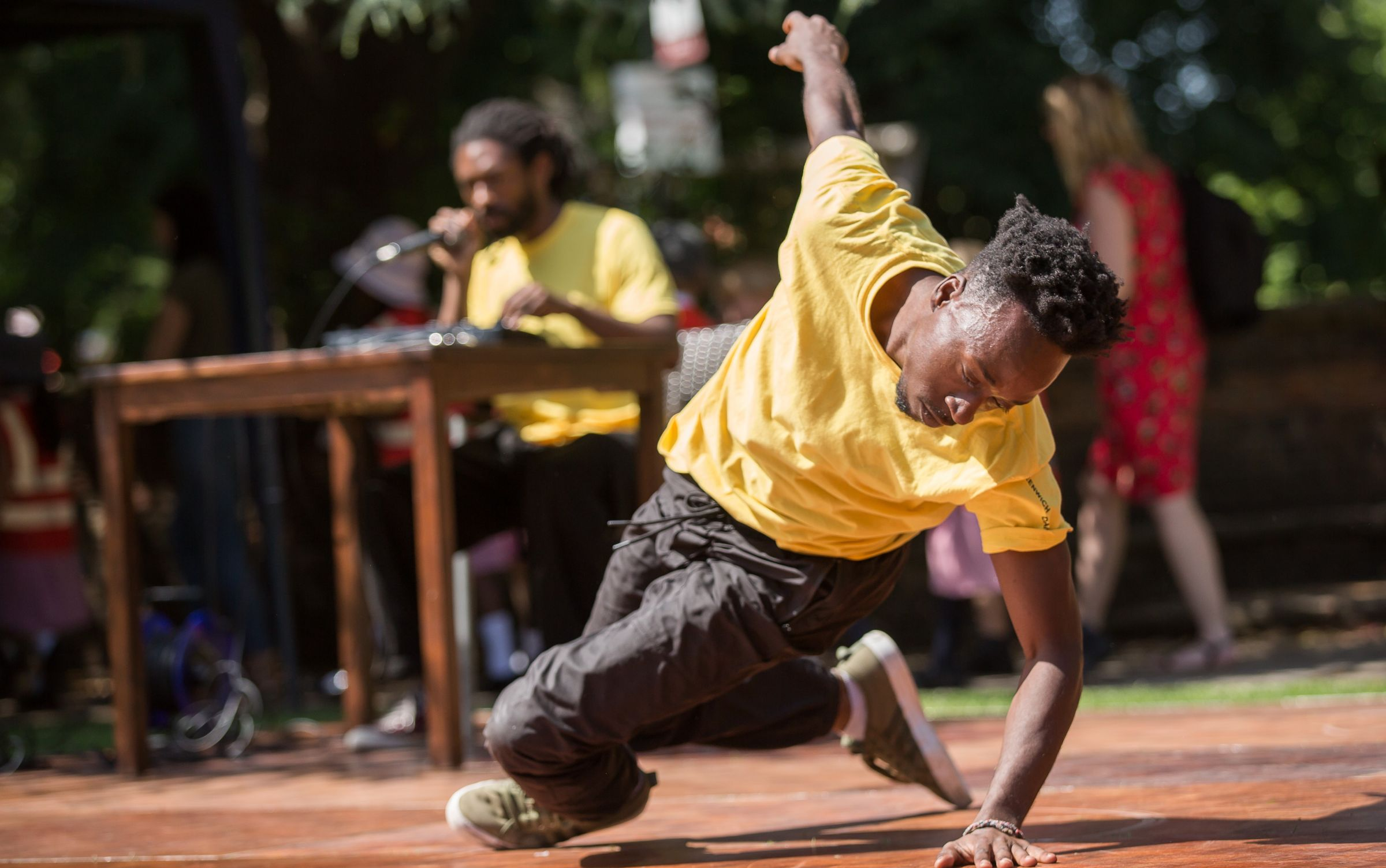 A dancer in a yellow tshirt performs outside