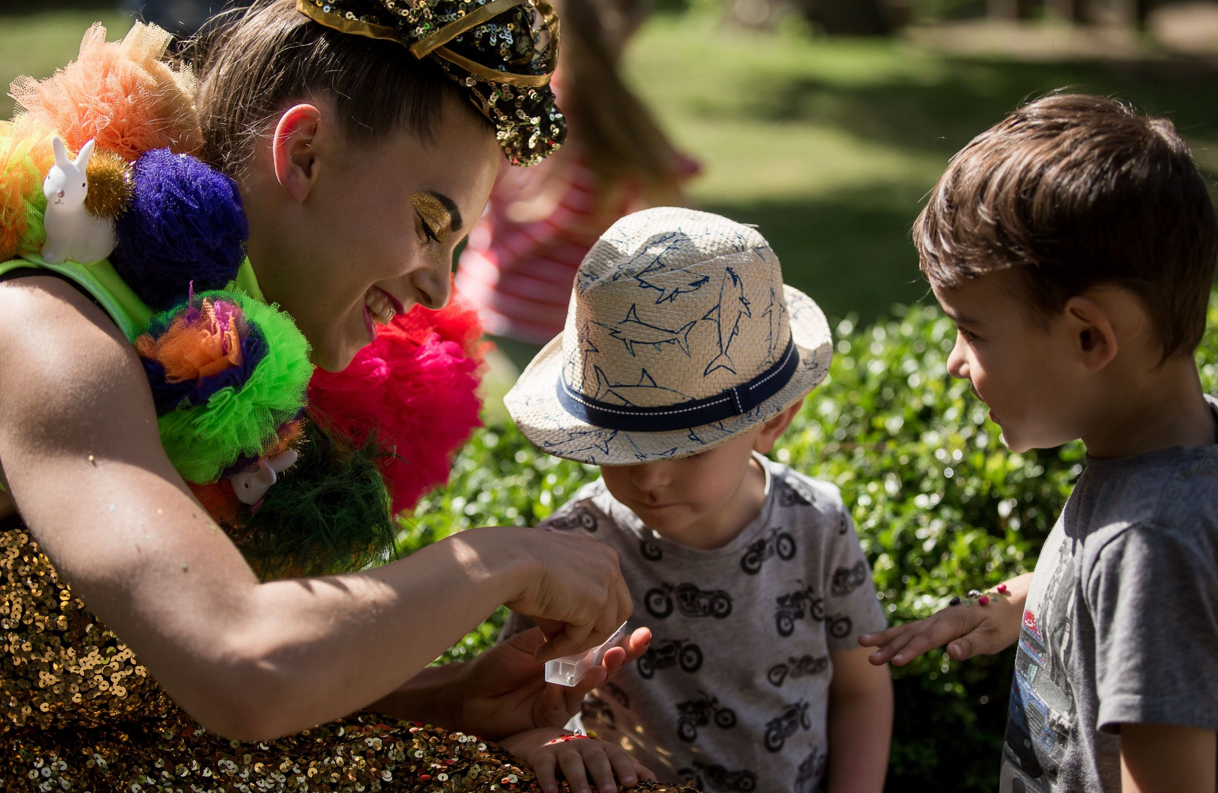 A female performer gives sweets to children