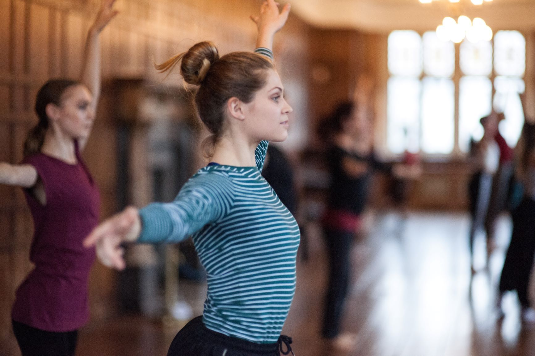 A dancer in a blue top with hair in a bun and arms out stretched