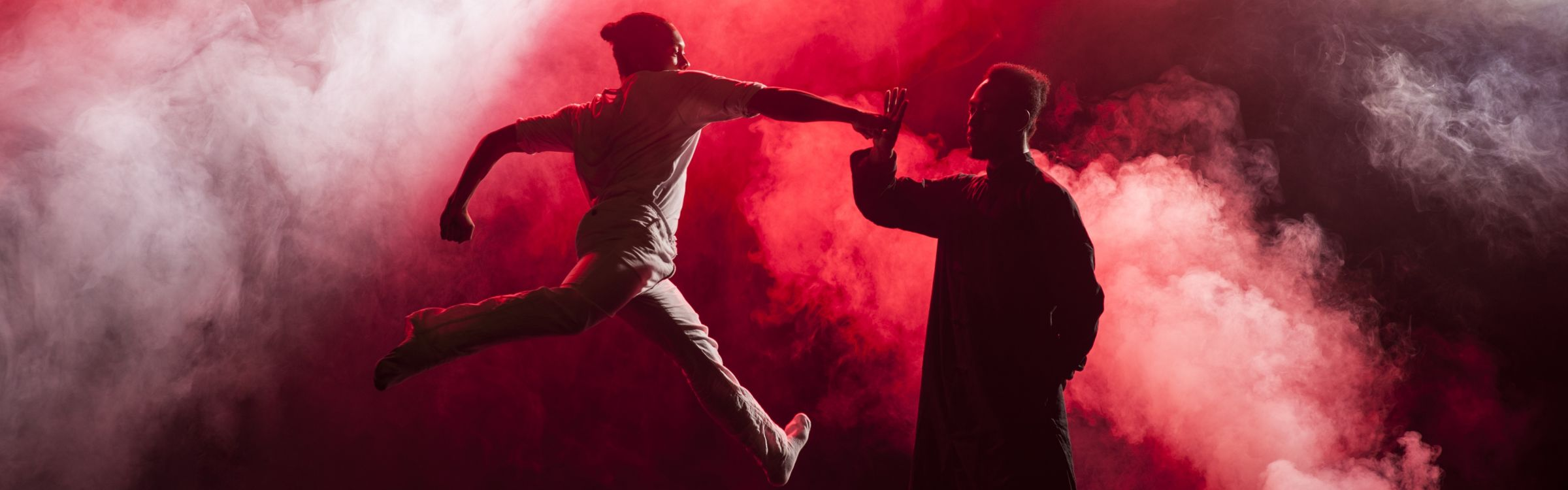 Two silhouetted dancers with a background of red smoke