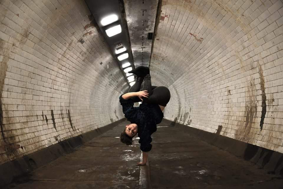 A hip hop dancer poses upside down in Greenwich foot tunnel