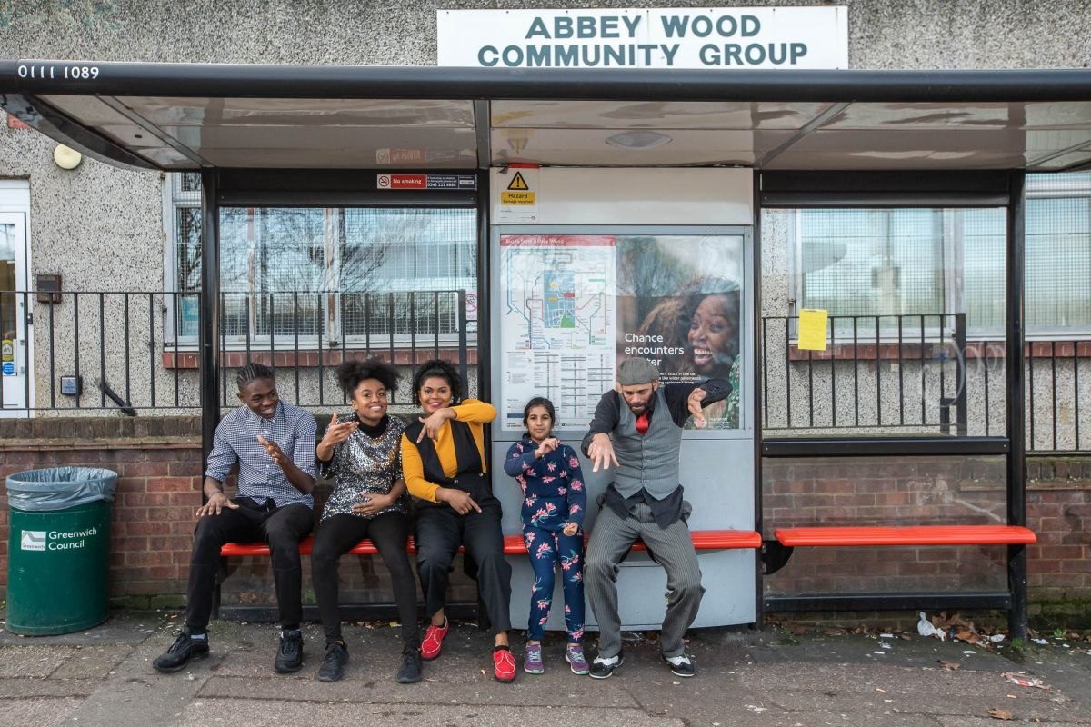 Five people at a bus stop in from of Abbey Wood Community Centre