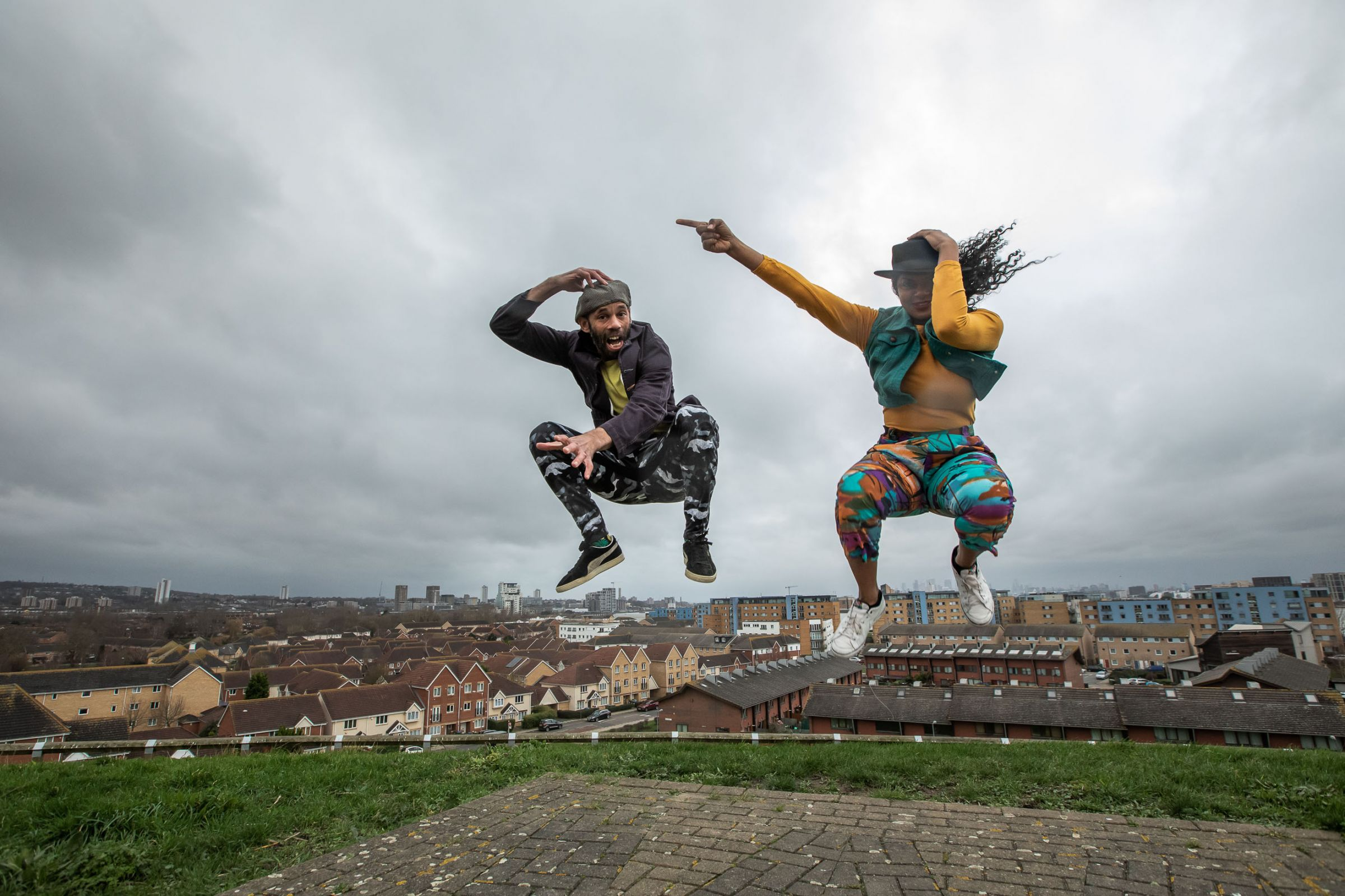 Two dancers jump up on top of a hill with houses in the background