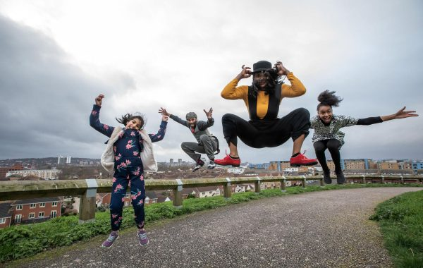 Four people on top of a hill jumping
