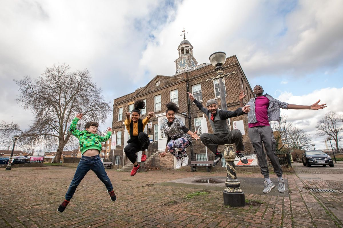Five people jumping in front of a grand looking building