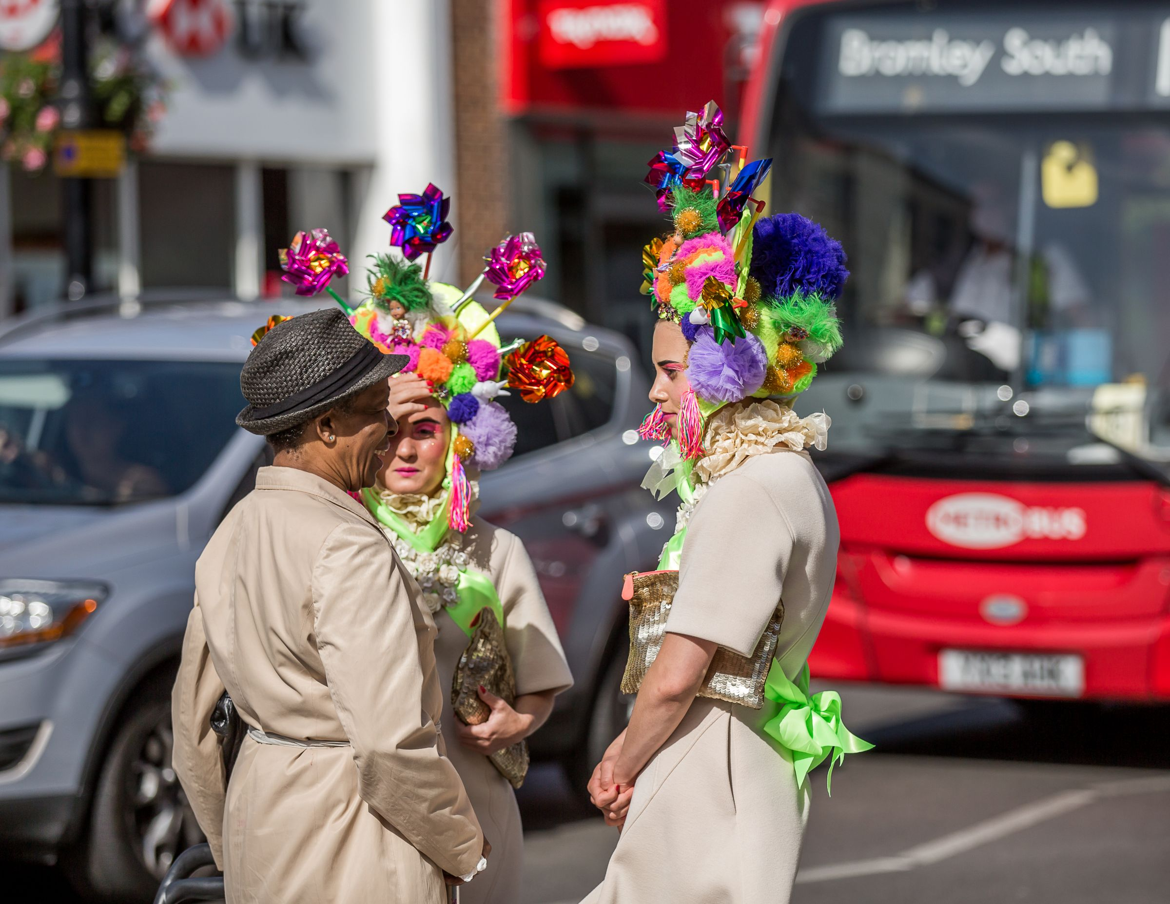 Two performers in elaborate costumes speak to a pedestrian