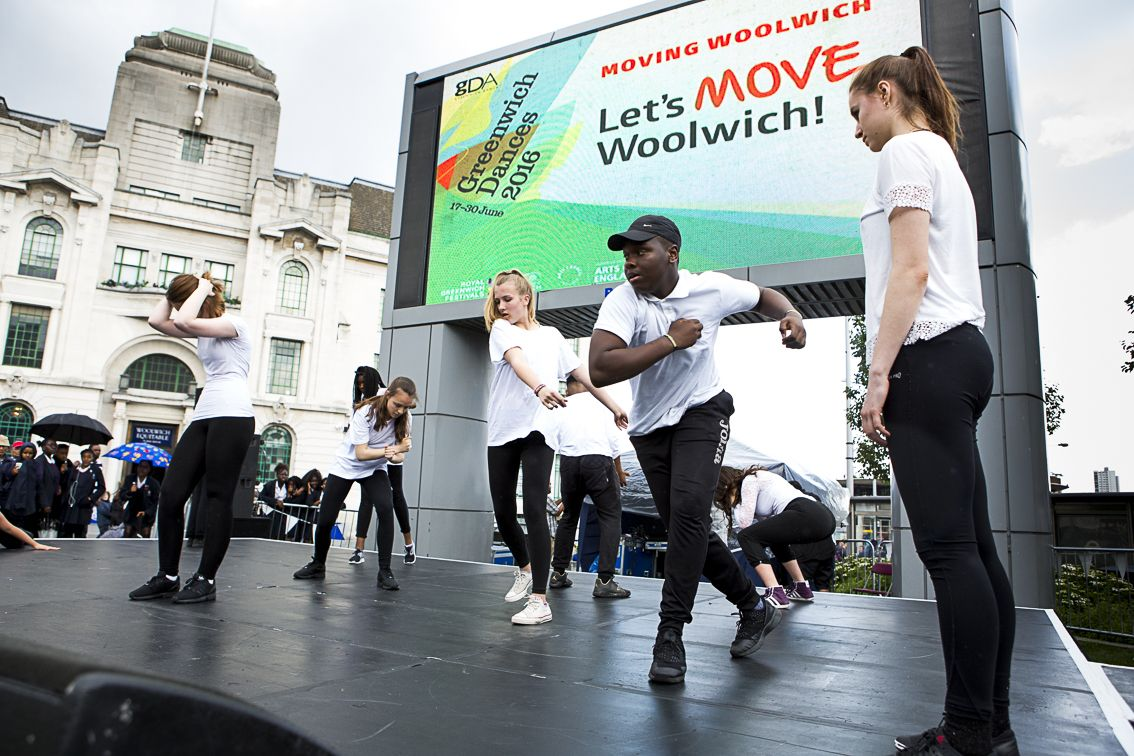 Young people performing on an outdoor stage with a screen in the background