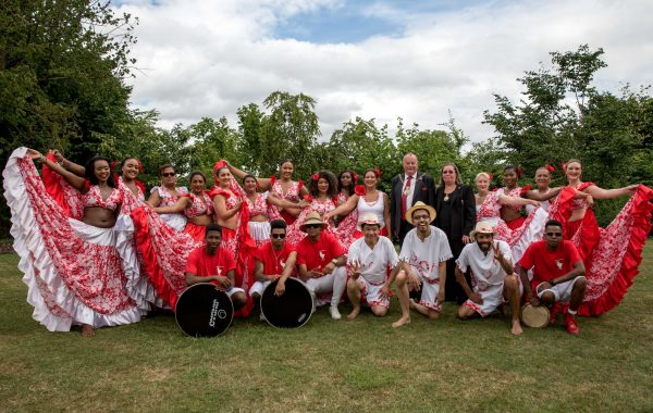A group of people in red and white costumes pose in a park