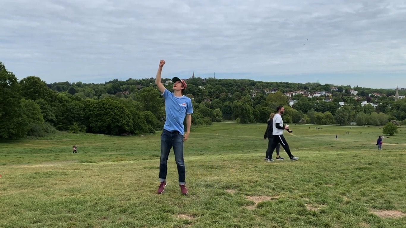 Young man standing on a hill with right hand raised