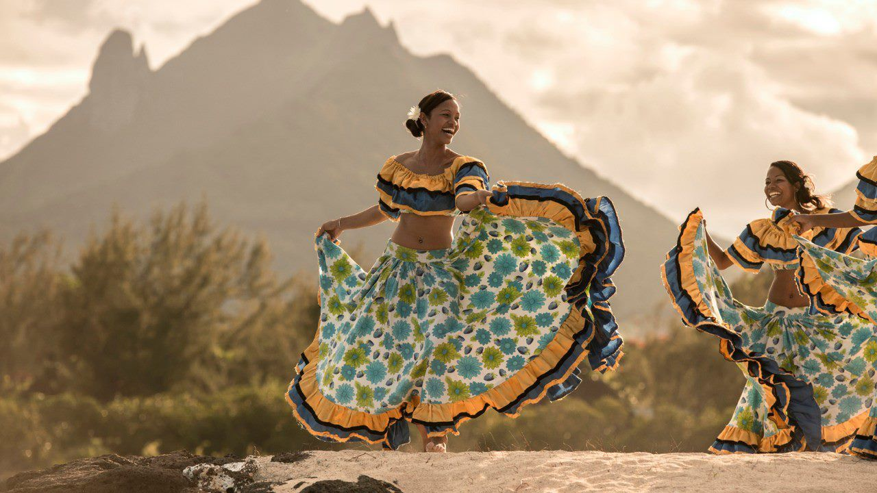Two dancers in Mauritian dress in front of a mountain