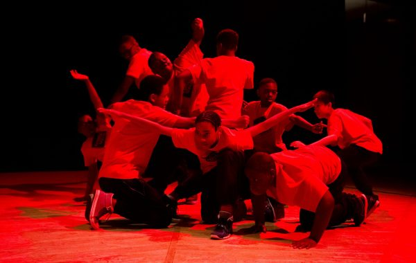 Children dancing on stage with red lighting