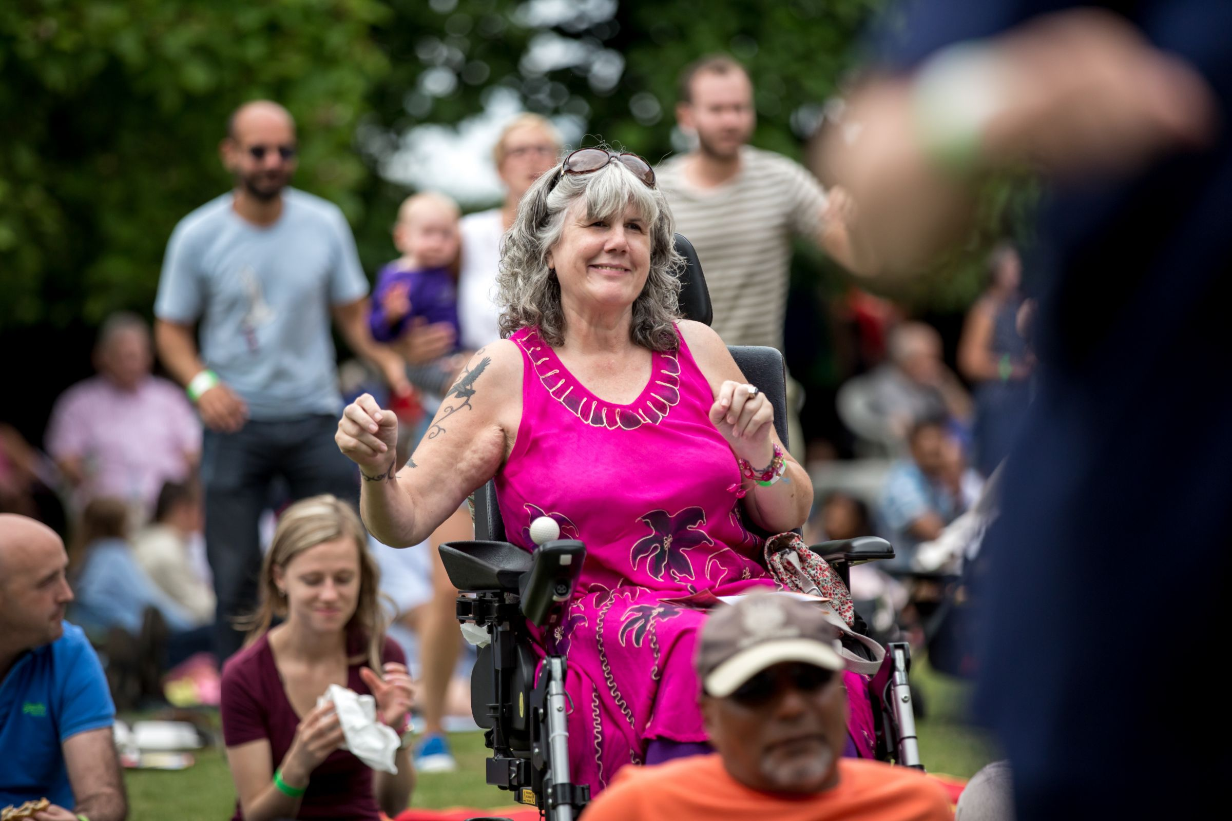 A woman in a wheelchair dances in a crowd of people