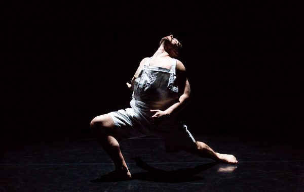 A male dancer on a blacked out stage