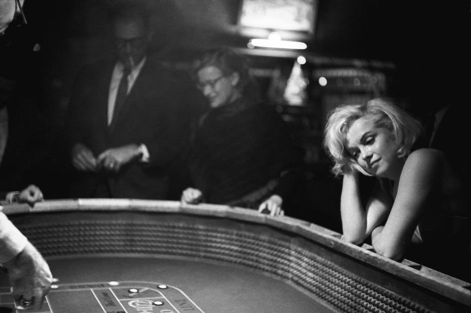 A black and white photo of Marilyn Monroe at a roulette table