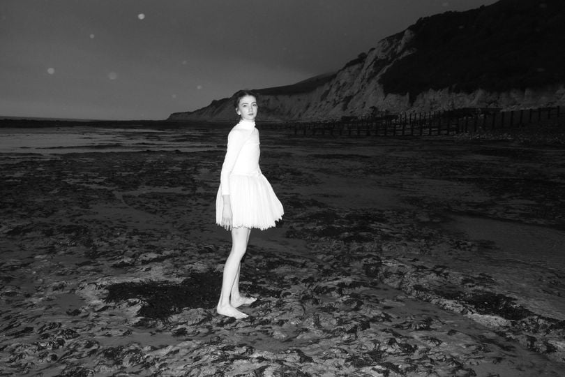 A black and white image of a woman on a beach at night