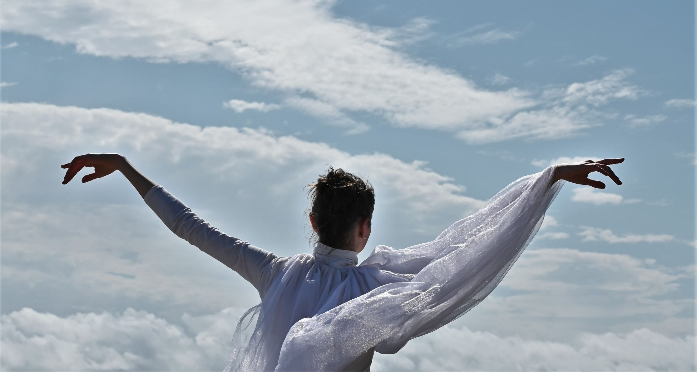 A woman facing the sky with arms outstretched