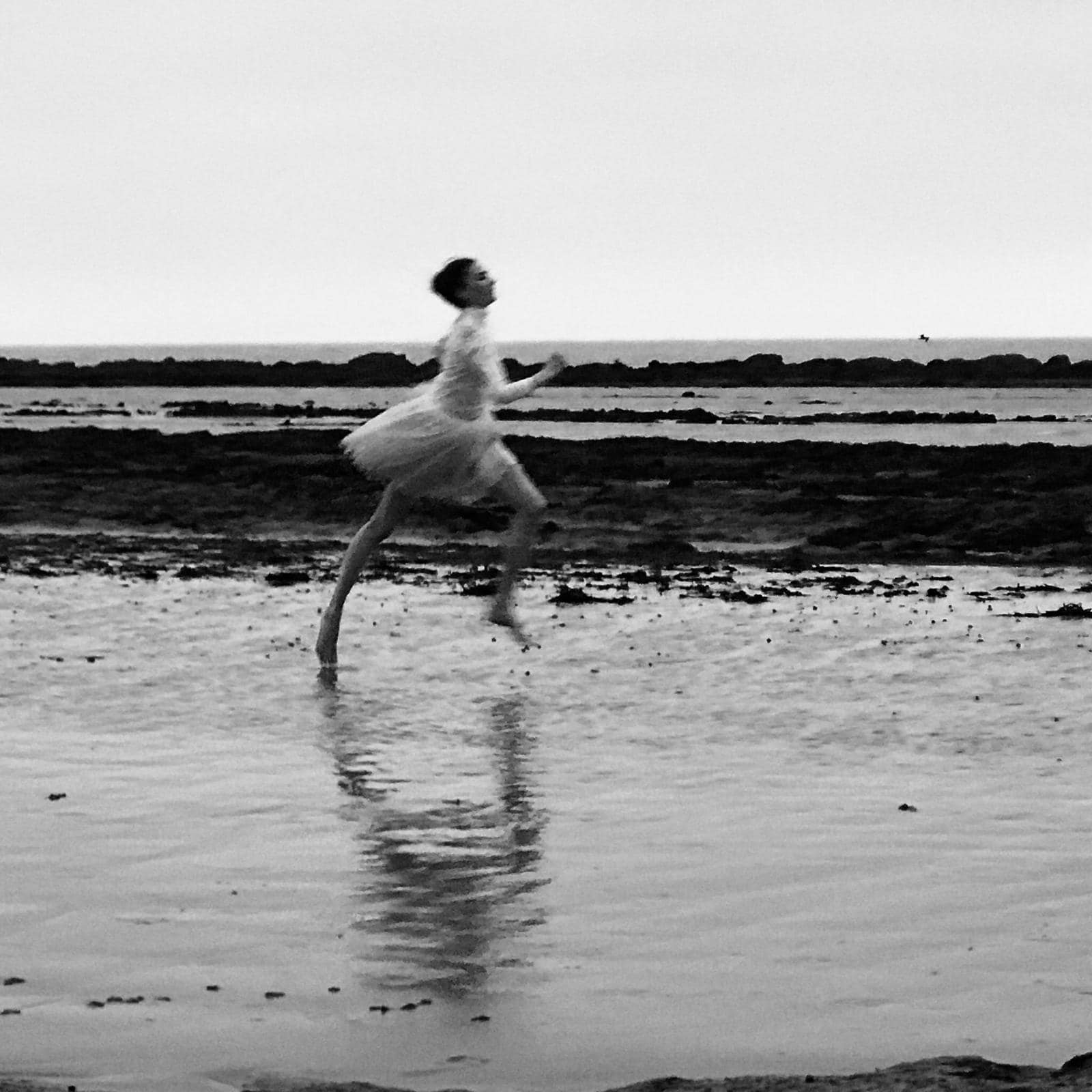 A black and white image of a woman running along a beach