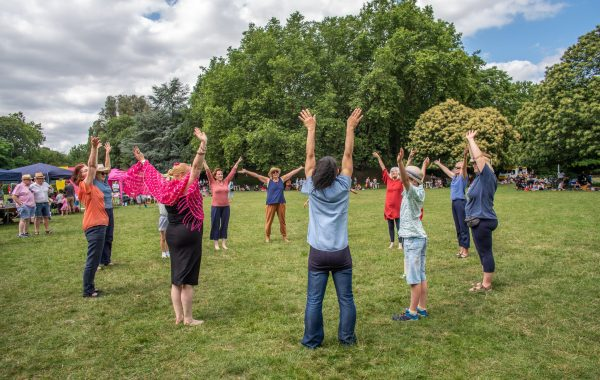 A group of people in a park stretch their arms up to the sky