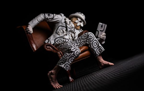 A dancer in a doodled costume poses on a leather chair