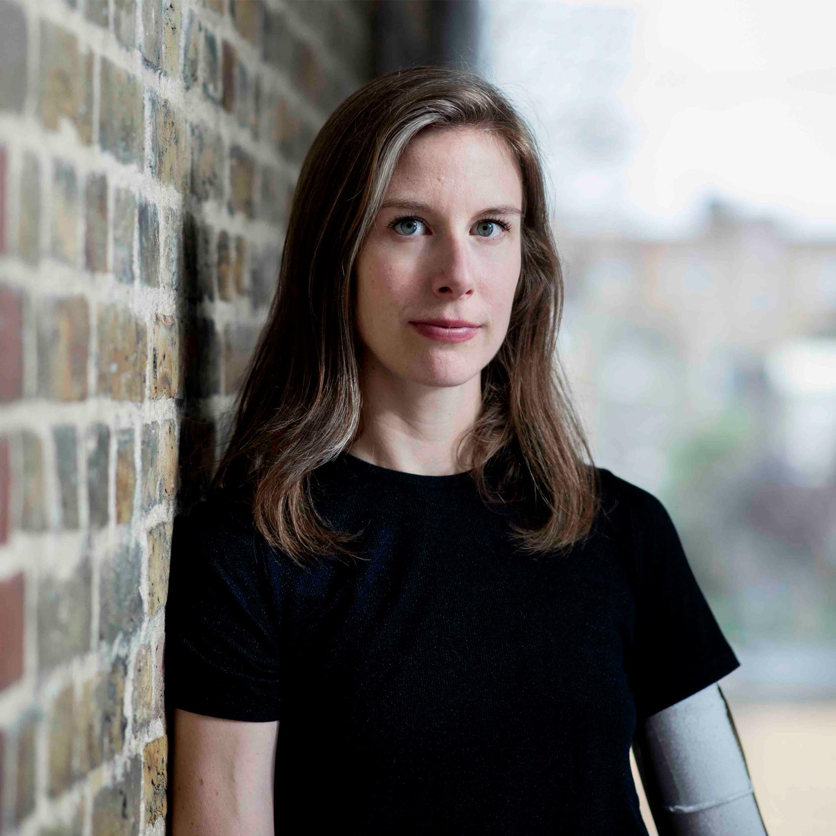Annie Hanauer colour head and shoulders photo leaning against a brick wall